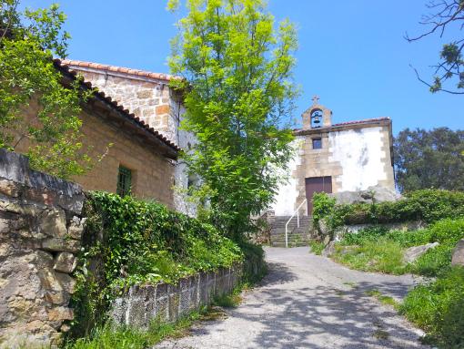 Fachada principal de la ermita de Santa Bárbara junto a un caserío.